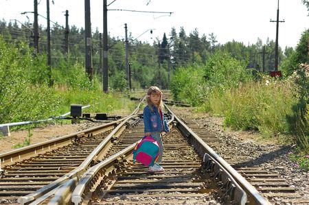 The little girl going with a backpack on railway rails Stock Photo