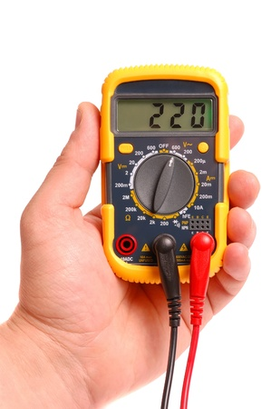 Hand with a digital multimeter on a white background   Stock Photo