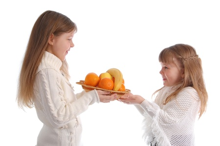 Two cheerful little girls with fruit on the white photo