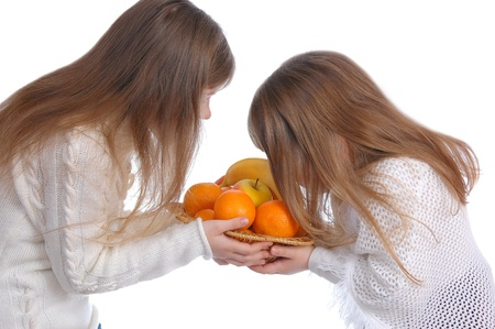 Two cheerful little girls looks at fruit on the white photo