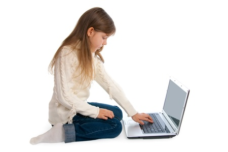 The sitting little girl with the laptop  Stock Photo