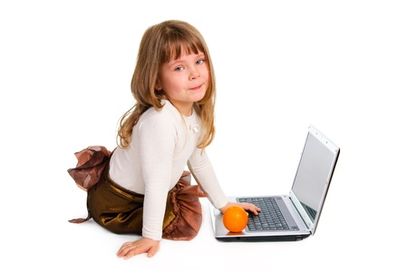 Sitting little girl with the laptop and fresh orange. White background.