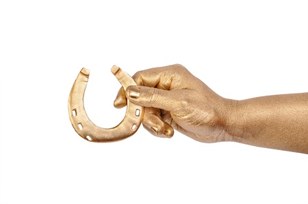 Mans golden hand with gold horseshoe. Isolated on white