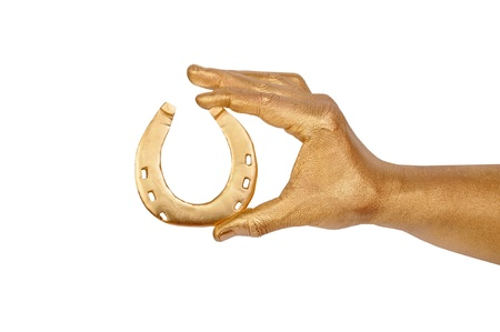 Mans golden hand with gold horseshoe. Isolated on white  photo