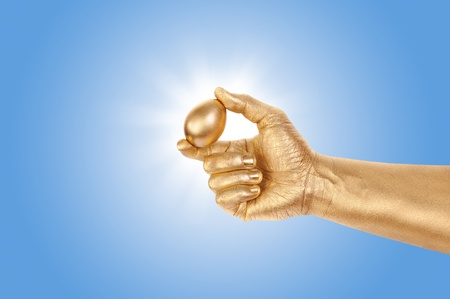 geste: Gold egg in a gold mans hand against the sky