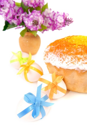 Easter cake and eggs decorated with bows. Vase with a lilac bouquet. Isolated on white photo