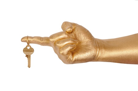 Mans golden hand with a key. Isolated on white  photo