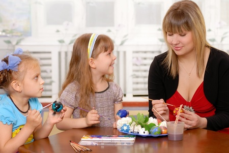 Young woman with children paints an Easter egg  Stock Photo