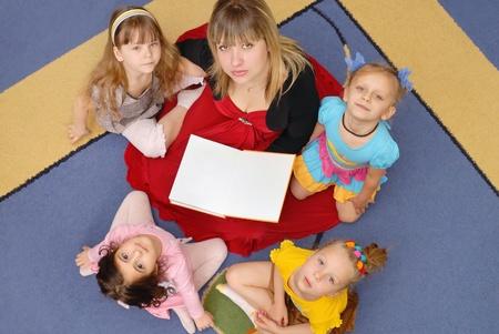 Tutor reads to children the book in a kindergarten