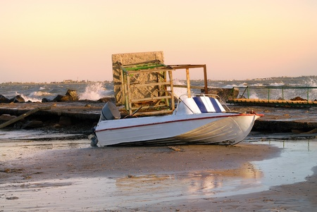 The broken tower rescuer and boat on seacoast after a storm at sunset Stock Photo