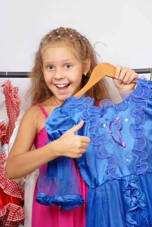 Little girl in shop of dresses and hand shows sign OK