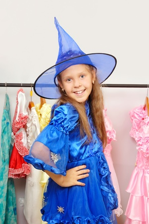 Little girl in shop of dresses tries on a  costume of a witch