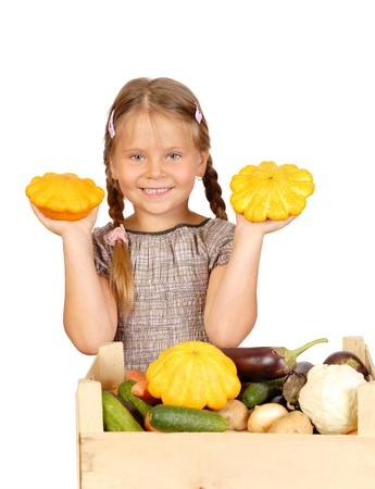 Little girl with vegetables. Isolated over white  Stock Photo