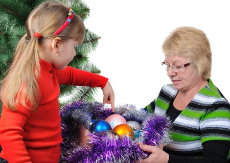 Grandmother with the grand daughter decorate a Christmas tree. Isolated over white