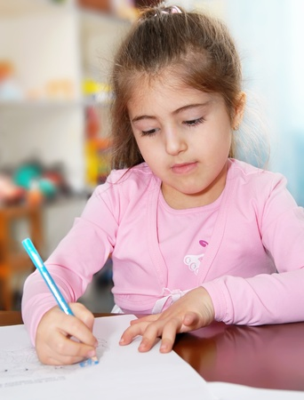 Schoolgirl works on her homework, writes on paper photo