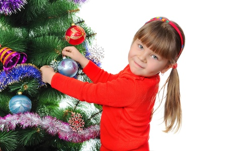 Girl decorates a fur-tree. Isolated on the white photo