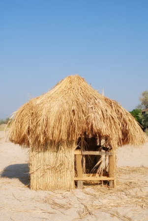 Hut from a dry grass ashore under blue sky photo