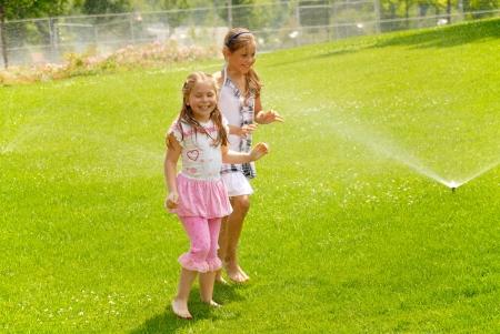 Girls run barefoot on a grass under splashes of garden watering photo