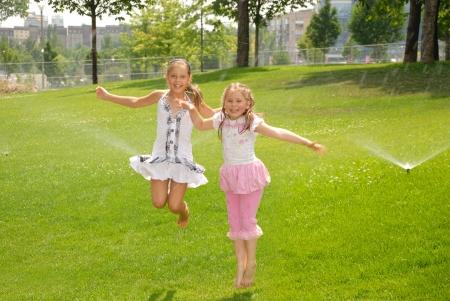 Two girls jump up barefoot in park under watering splash photo