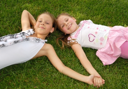 Two little girls lie on a green grass and to hold a hand photo