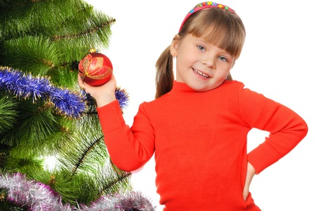 Little girl decorates a fur-tree  Isolated on the white photo