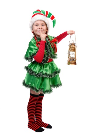 Girl in suit of Christmas elf with oil lamp with finger over her mouth  Isolated on a white photo