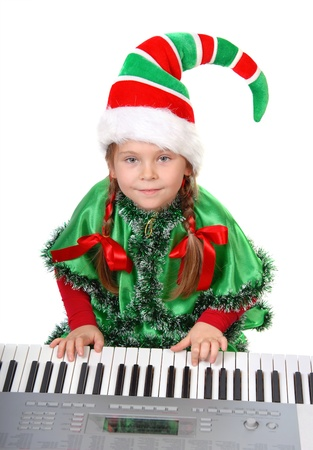 Girl - Santa s elf plays a synthesizer  Isolated on a white photo