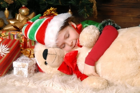 Girl - the Christmas elf sleeps under a fir-tree and embraces a toy bear