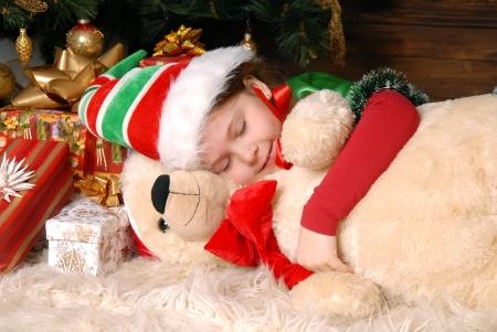 Girl - the Christmas elf sleeps under a fir-tree and embraces a toy bear