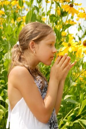 Girl in a garden smells a yellow flower