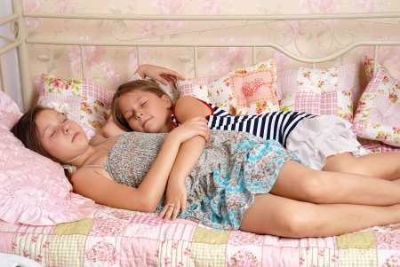 Two little girls - sisters sleep in a bed photo