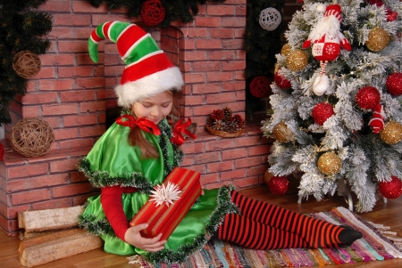 Girl - the Christmas elf with a gift near Xmas fir-tree and fireplace Stock Photo
