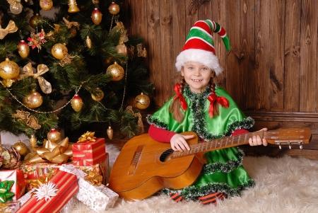 Girl - the Christmas elf with a guitar near Xmas fir-tree