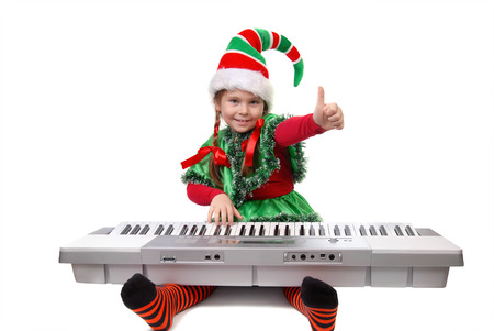 Girl girl in suit of Santa elf play on synthesizer
