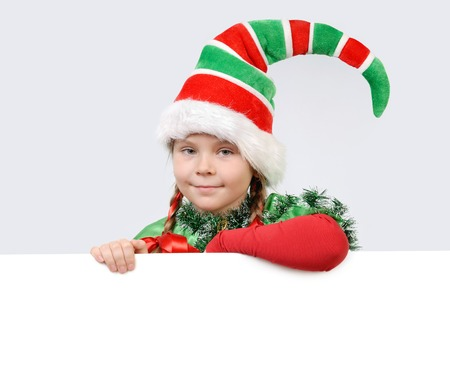 Girl in suit of Christmas elf with the white banner on a grey background photo