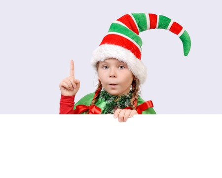 Little girl in suit of Christmas elf with the white board. photo