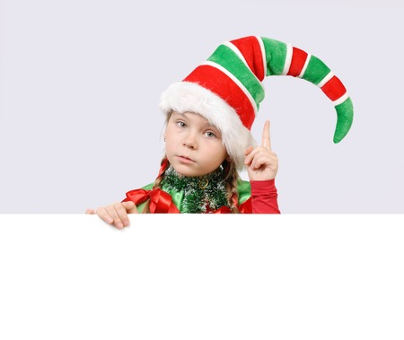 Little girl in suit of Christmas elf with the white board photo
