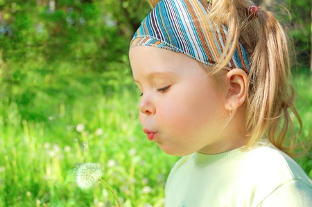 blows: The girl on a lawn blows on a dandelion.