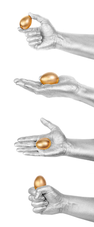 gold eggs: Set from 4 Gold Eggs in a silver mans hand. Isolated on white. Business success concept symbols. Stock Photo