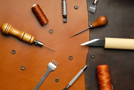 Leather crafting DIY tools lies on natural brown leather. 스톡 콘텐츠