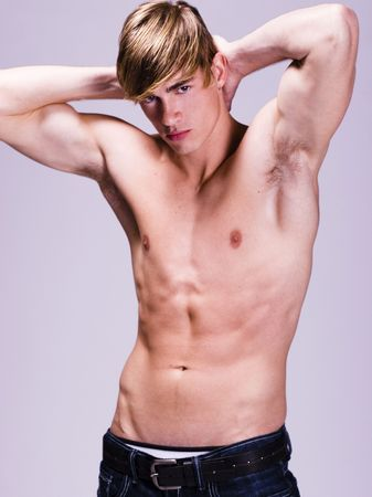 Shirtless young man with his arms behind his head