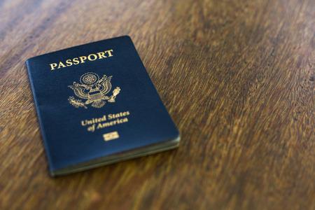 One blue American passport on wooden desk Imagens