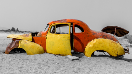 rusty car: Old and rusty car wreck without wheels in the desert of Namibia