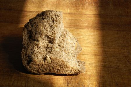 starvation: A piece (slice) of bread on the desk in sun light. Very interpretations (poverty, starvation, usw)  Stock Photo