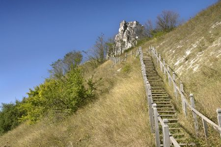 wonderfull: Wood stairs on the slope of Wonderfull Hills. Hot summer day. Green slopes and blue sky. On the background rock where placed medieval monastery Stock Photo