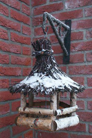 Wooden bird feeder in winter with snow                photo