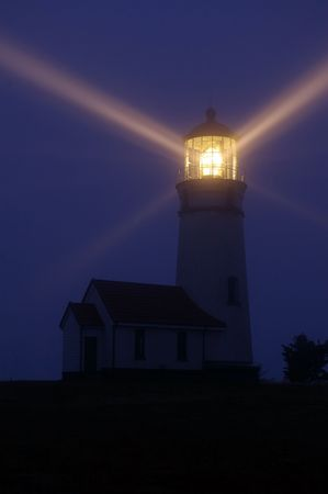 lighthouse with beam: Lighthouse at night Stock Photo