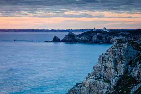 Lighthouse at night on a rocky cliff in France at sunset photo