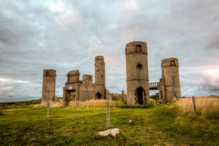 crumbled: Old stone ruins of a castle or house or mansion in medieval France with a dramatic grey cloudy sky in the background and bright green grass in the foreground. This is a high dynamic range image.
