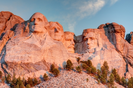 Mount Rushmore National Memorial on a clear blue sunny morning during sunrise showing all four presidents faces in HDR